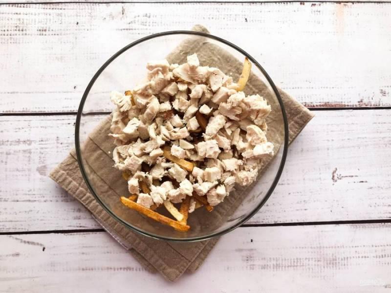 Вареную курицу мелко нарежьте и добавьте к картофелю фри.