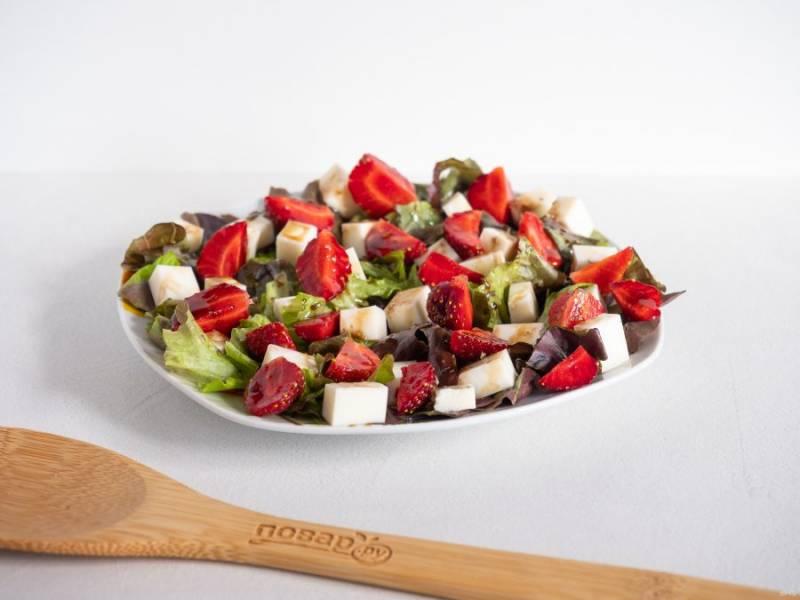 Клубнику очистите от плодоножек, нарежьте четвертинками и выложите на салат. Полейте оставшимся соусом и подавайте к столу.