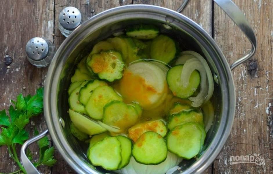 В горячий маринад выложите подготовленные лук и огурцы. Затем добавьте немного куркумы. Не переусердствуйте, ведь она может придать блюду горечь.