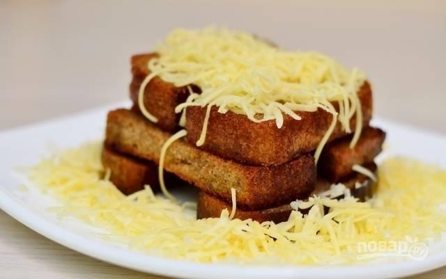 Выложите гренки на тарелку. Натрите сверху сыр. Приятного аппетита!