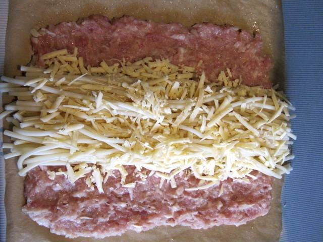 Фарш смешиваем с яйцо и измельченным луком и чесноком, солим и перчим его, макароны аккуратно, чтобы не повредить, отвариваем в слегка подсоленной воде до полуготовности. Теперь смазываем бумагу для выпечки растительным маслом и выкладываем на нее фарш в виде прямоугольника. По середине прямоугольника кладем макароны и посыпаем их тертым сыром.