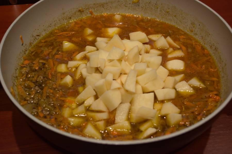 Добавьте нарезанный картофель. Перемешайте. Подлейте воды при необходимости. Накройте сковороду крышкой, уменьшите огонь и тушите до готовности картофеля. Периодами помешивайте. При необходимости подливайте жидкость.