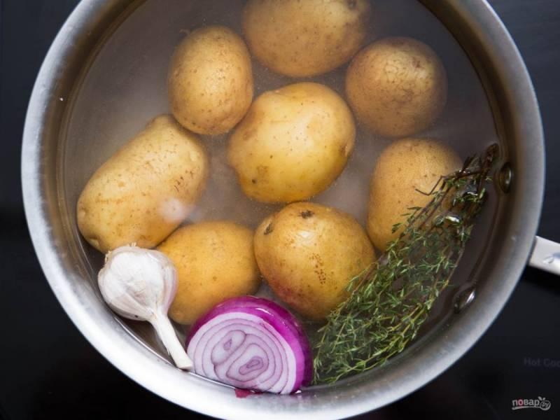2.Картошку мою и заливаю водой, добавляю 1 луковицу, тимьян и 4 зубчика чеснока, насыпаю столовую ложку соли, варю до готовности.