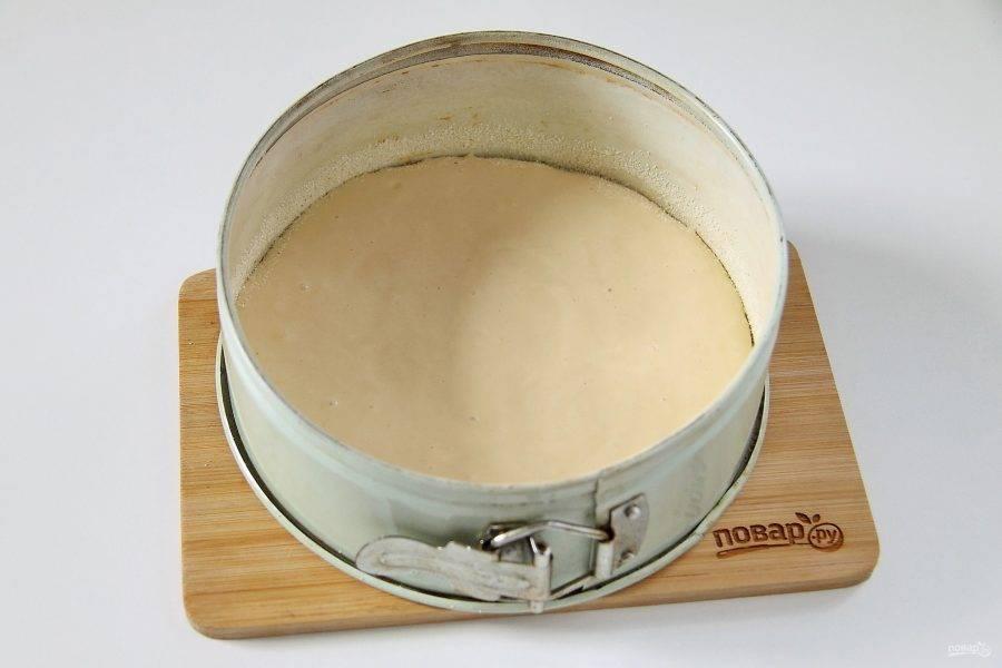Форму для выпечки смажьте маслом. Дно и бока присыпьте мукой или манкой и вылейте примерно 2/3 теста.