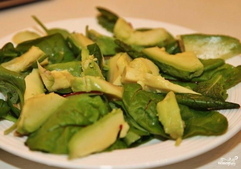 На тарелку или в салатницу выкладываем зеленые листья салата, сверху кусочки авокадо.