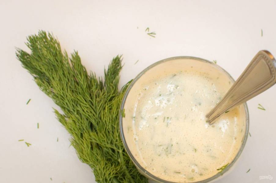 5. Теперь нужно приготовить соус: смешайте растительное масло с солью, яйцом и горчицей. Взбивайте погружным блендером минут 5, после чего добавьте укроп и чеснок. Взбивайте еще минуты 3. В результате у вас получится домашний майонез. Добавьте в него немного лимонного сока и перемешайте.