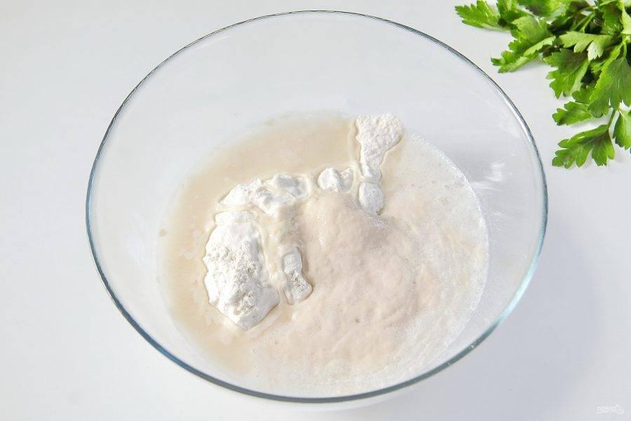 3. В глубокую миску просейте муку, добавьте соль и подошедшие дрожжи.