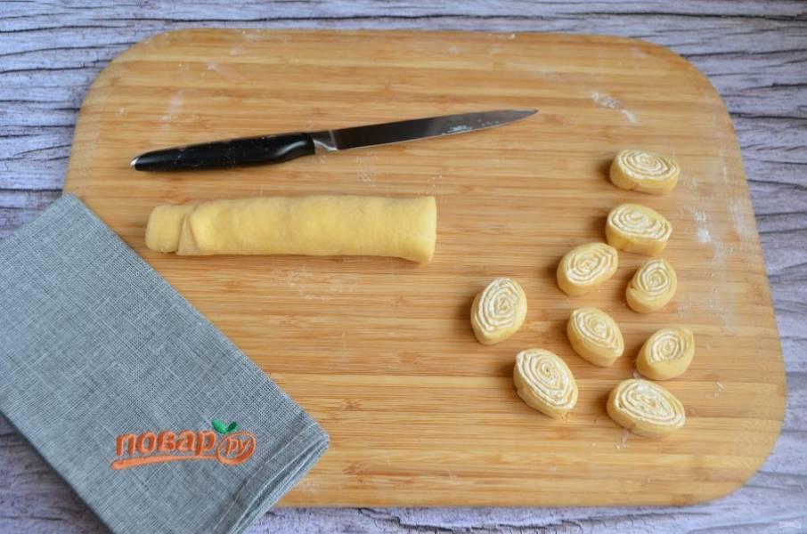 10. Сверните тесто с сыром в плотный рулетик, скрепите края, нарежьте рулет на кусочки - маленькие рулетики.