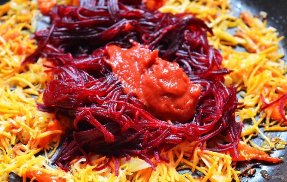 На растительном масле обжариваем лук и морковь до золотистого цвета, затем отправляем к ним свеклу и томатную пасту, жарим еще минут 5.