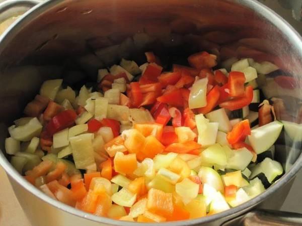 Болгарские перцы моем, удаляем сердцевину с семенами. Нарезаем кубиками и отправляем в кастрюлю к кабачкам.