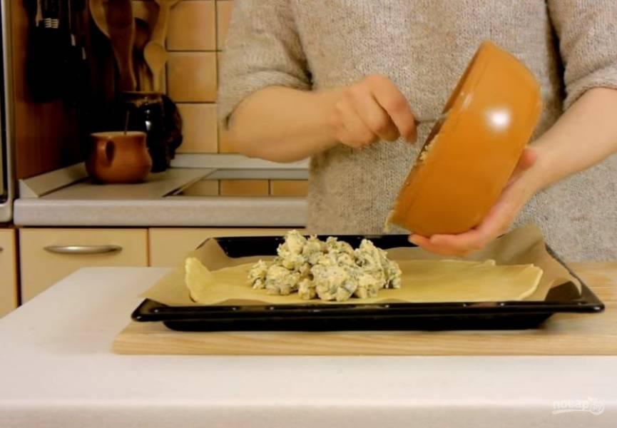 4. К начинке добавьте половину тертого твердого сыра. На посыпанной мукой доске раскатайте тесто в круг толщиной 3-4 мм. Перенесите тесто на бумагу для выпечки, выложите начинку и сформируйте галету.