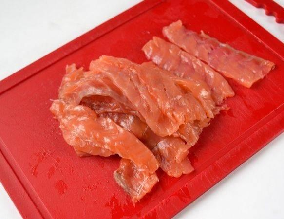 3. Рыбу (в данном варианте семга, но может быть и другая) очистить от кожи и костей, если имеются. Нарезать тонкими и длинными полосочками. Чтобы рыбка резалась хорошо, ее можно отправить на 3-5 минут в морозильную камеру.