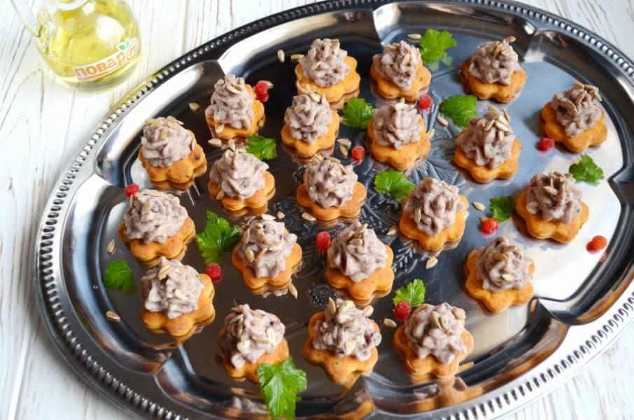 12. Фасолевый паштет переложите а кондитерский мешок, поставьте насадку с крупным отверстием, отсадите паштет на крекеры. Украсьте семечками или зернами граната, зеленью.