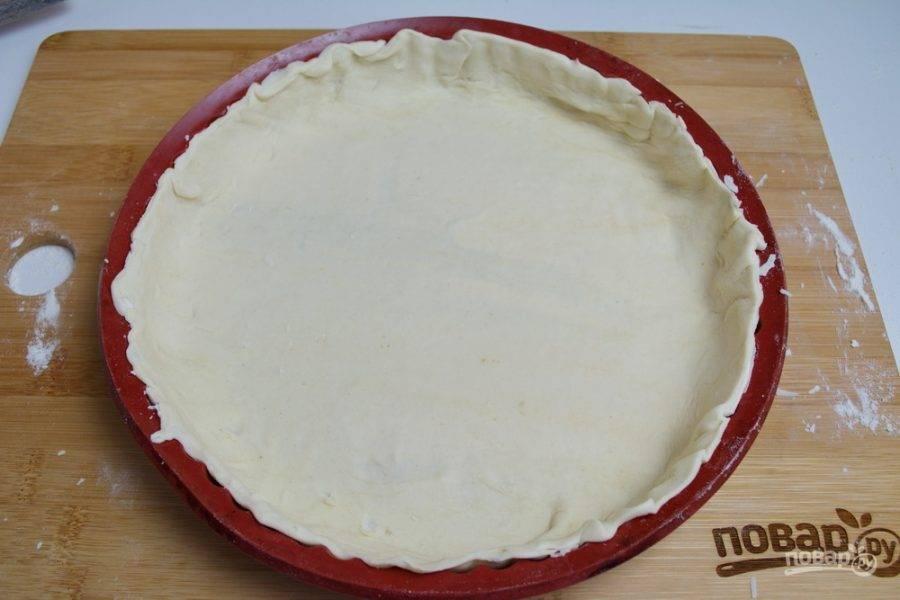 Тонкое тесто выложите в форму, лишнее обрежьте.
