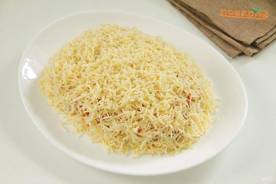 Затем натертый сыр. Сыром также посыпаем  и бока со всех сторон, смазываем салат майонезом.