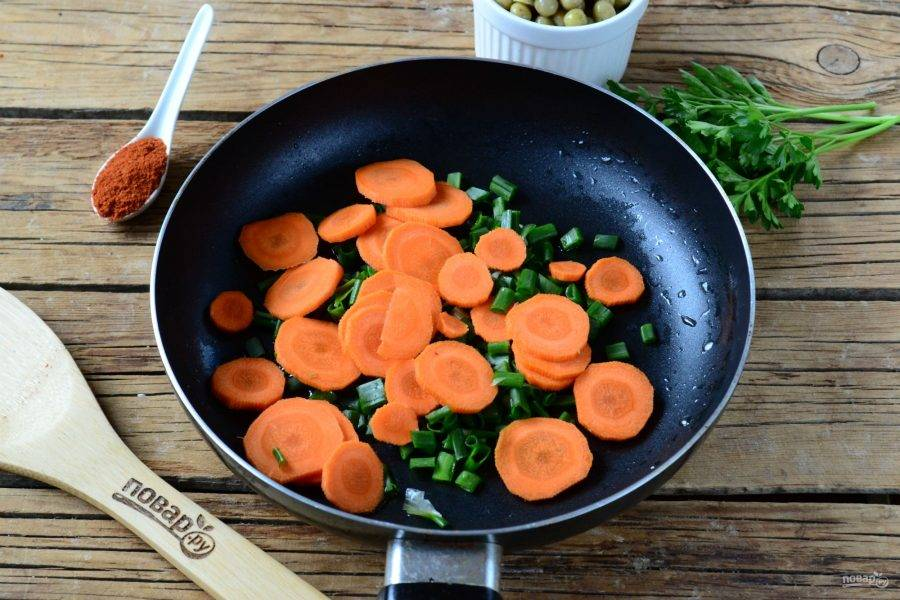 Одновременно с этим на другой сковороде обжарьте измельченный зеленый лук и порезанную кружочками морковь. Готовьте несколько минут.