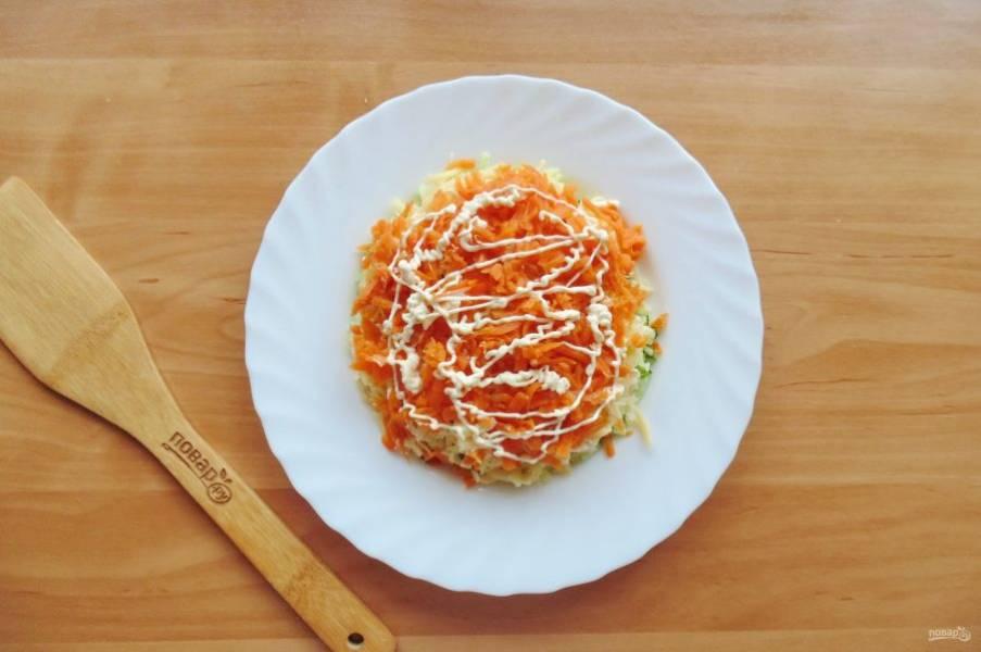 Морковь натрите на терке. Выложите следующим слоем.