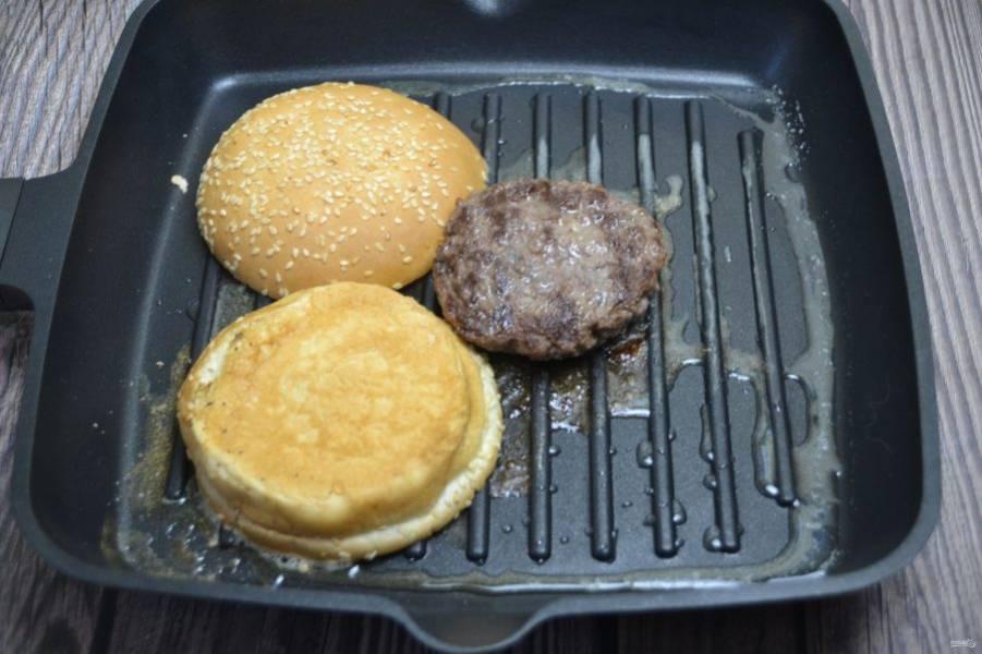 Обжарьте мясную котлету на сковороде гриль, рядом выложите булочку, разрезанную пополам.