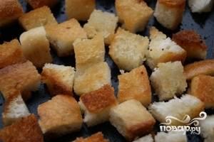 Батон освободить от корки и нарезать кубиками со стороной примерно 1 сантиметр. Выложить на противень, сбрызнуть маслом и поджарить до золотистого цвета. Можно это сделать и на сковороде, главное, чтобы крутоны не получились слишком жирными.