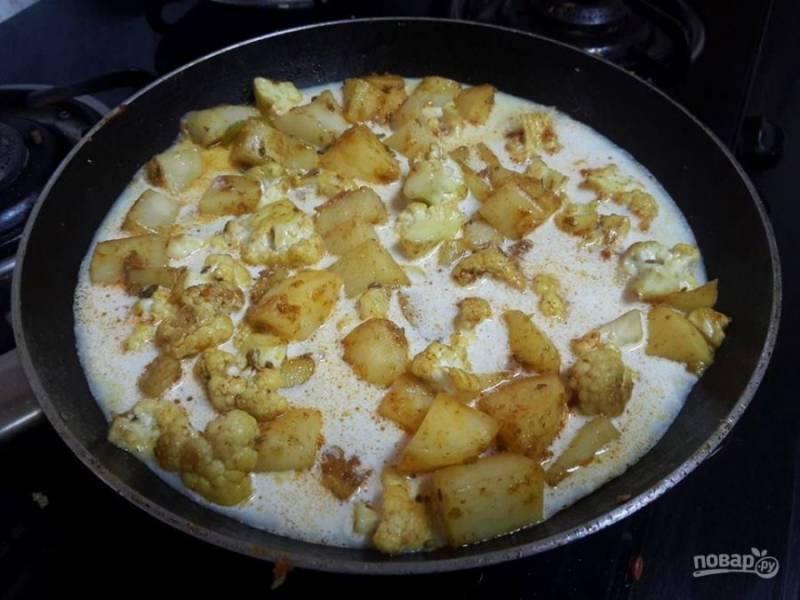 3. Влейте к овощам молоко, добавьте соль и перец по вкусу, готовьте картофель и капусту до мягкости на среднем огне под закрытой крышкой.