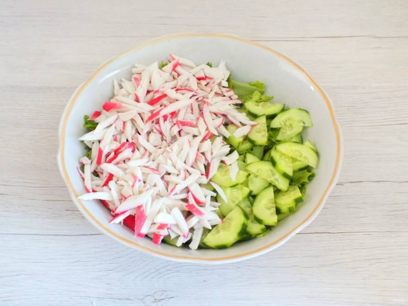 Крабовые палочки нарежьте тонкой соломкой, переложите в салатник.