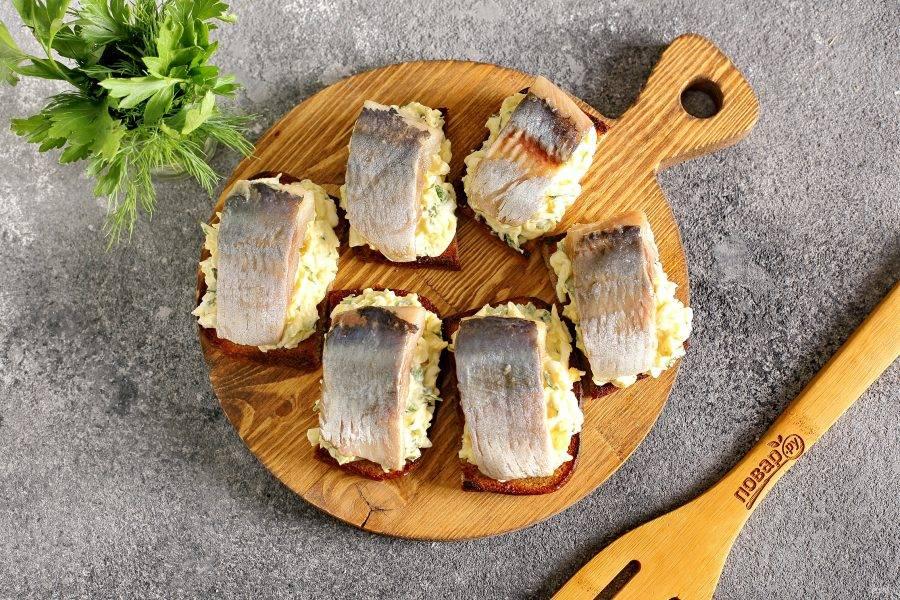 Сверху выложите по 1 или 2 кусочка филе сельди.