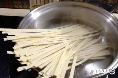 Пшеничную лапшу необходимо отварить в кипящей подсоленной воде по инструкции на упаковке. Затем откинуть на дуршлаг и промыть холодной водой.