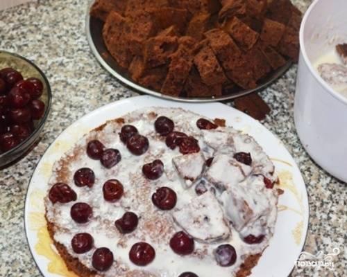 Основу торта смажем кремом, выложим вишни (у меня консервированные). Большую часть бисквита нарезаем на небольшие кусочки, окунаем в крем и выкладываем на основу.