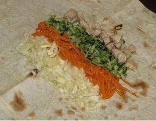 На лаваш выложите капусту, морковь, огурцы и курицу.