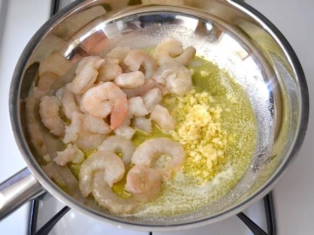 2. Креветки промойте, позвольте стечь воде. Затем выложите на сковороду. Туда же отправьте чеснок. Огонь - средний.