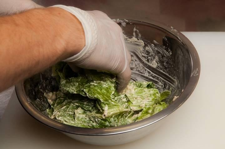 """Выкладываем листья в миску, добавляем соус """"Цезарь""""."""