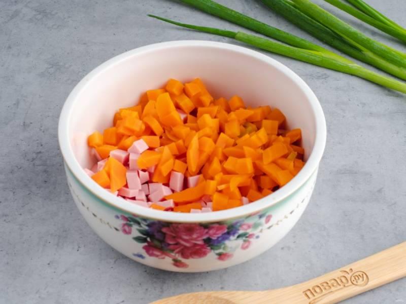 Нарежьте небольшими кубиками колбасу и морковь.