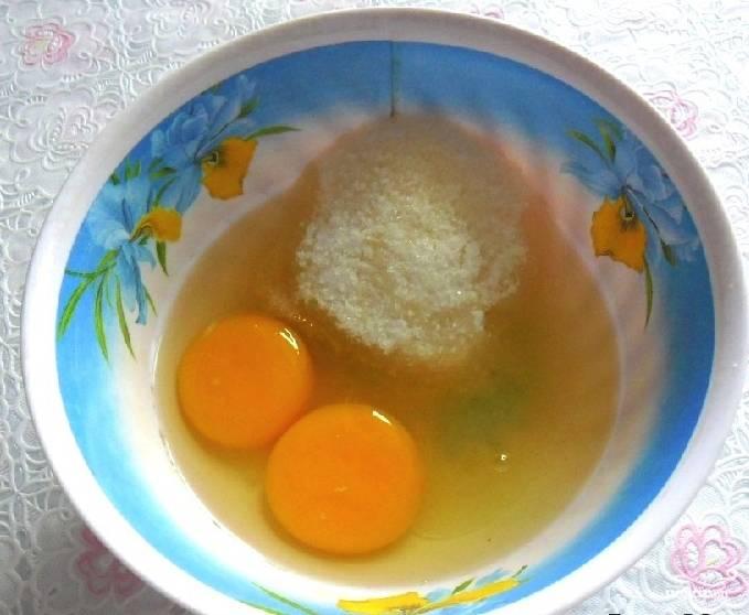 В миске разбейте яйца. Туда же отправьте сахар и хорошо размешайте его с яйцами при помощи вилки или блендера. Сюда же положите щепотку соли. Дождитесь, пока сахар немного растает.
