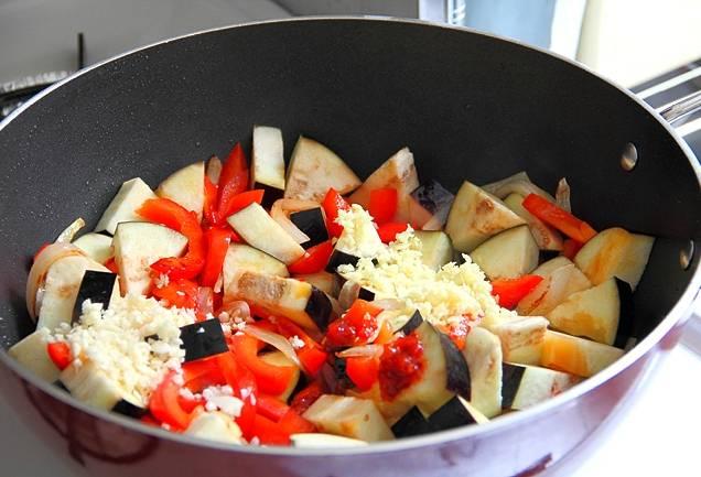 Разогреваем сковородку. Наливаем в неё подсолнечное масло. Обжариваем лук. Докладываем болгарский перец, баклажаны, тертый имбирь, чеснок и чили-пасту, обжариваем все это пять минут на сильном огне, помешивая.