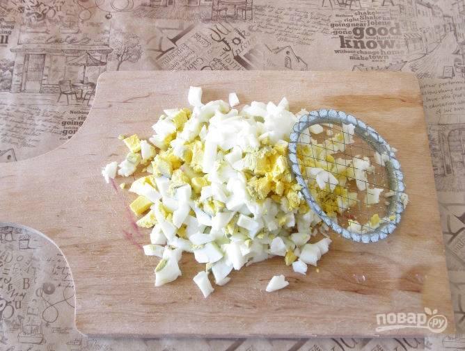 Нарежьте яйца мелкими кубиками.