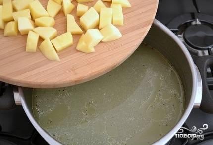 5. Когда бульон сварился, удалите из него окорочок и луковицу. Подсолите, добавьте молотого перца (при желании). Теперь положите в бульон картофель.