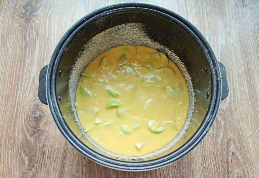 Чашу для мультиварки смажьте растительным маслом и посыпьте панировочными сухарями. Вылейте в чашу тесто с яблоками.