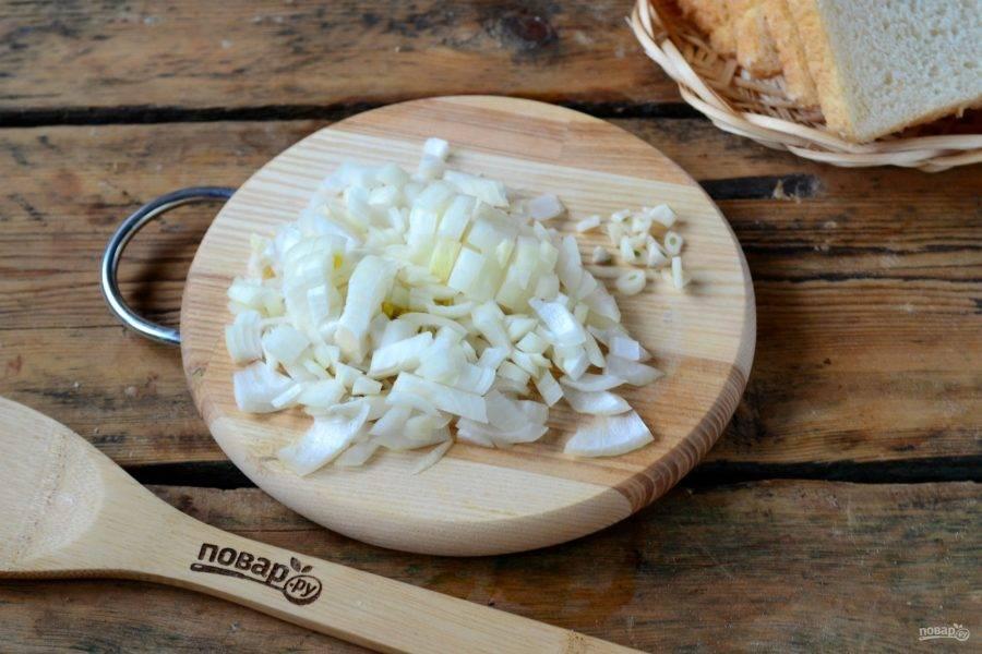 Начнем с приготовления соуса. Луковицу и несколько зубчиков чеснока измельчите ножом. Выложите на сковороду с разогретым растительным маслом и жарьте до легкого золотистого оттенка.