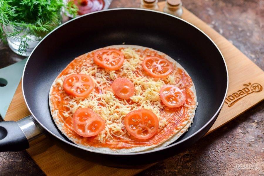 Снова посыпьте немного лаваш сыром, выложите нарезанные кружочками помидоры.