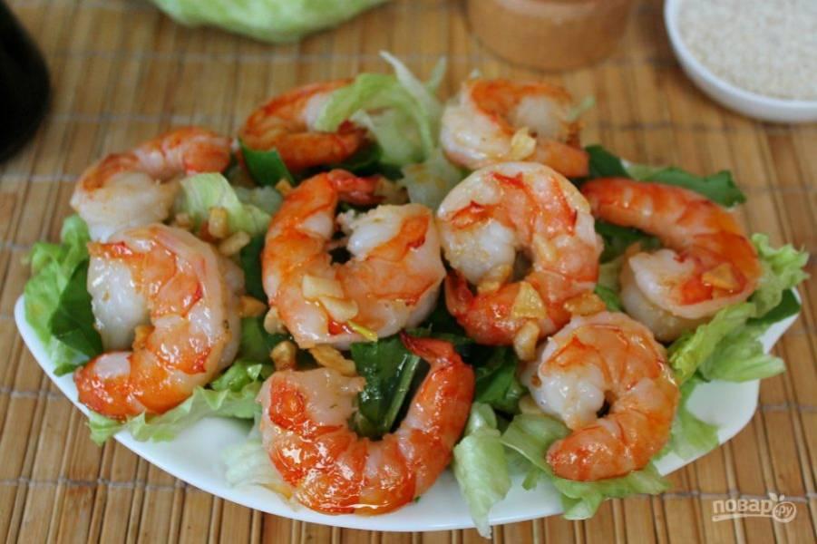 Горячие креветки с чесноком и маслом выкладываем на салат.