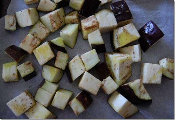 2. Нарежьте баклажан кубиками по 2-2,5 см, выложите в миску, добавьте немного оливкого масла (2-3 ст. ложки), соли, перца, перемешайте руками, а затем выложите на застеленный пергаментом противень.