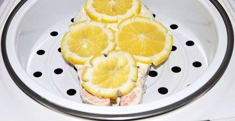 Кладем рыбу в емкость для варки на пару, смазываем сметаной, а сверху кладем дольки оставшегося лимона.