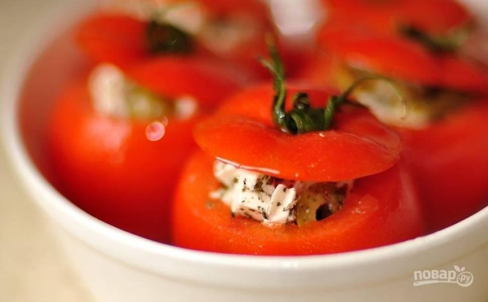 """Выложите начинку из сыра, оливок и базилика в помидоры. Прикройте их """"крышечками"""" из срезанных верхушек. Выложите томаты в жаропрочную форму и полейте оливковым маслом."""