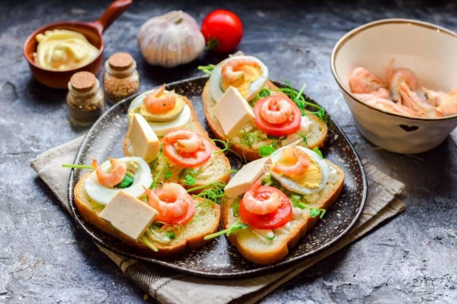 Вареные креветки очистите и разложите на бутерброды, добавьте по кусочку сыра и подавайте к столу.