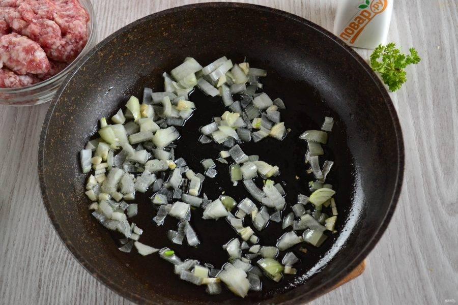 В сковороде разогрейте растительное масло, добавьте лук и чеснок. Обжаривайте, чтобы лук стал прозрачным.