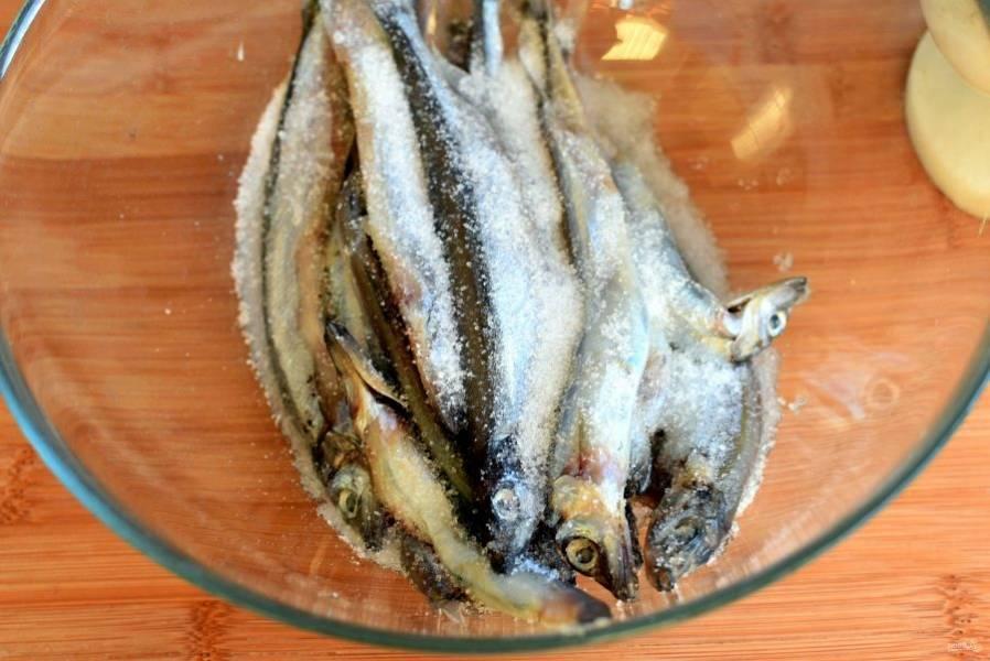 Рыбу выложите в просторную стеклянную миску и посыпьте смесью соли и сахара. Перемешайте, стараясь равномерно распределить специи.