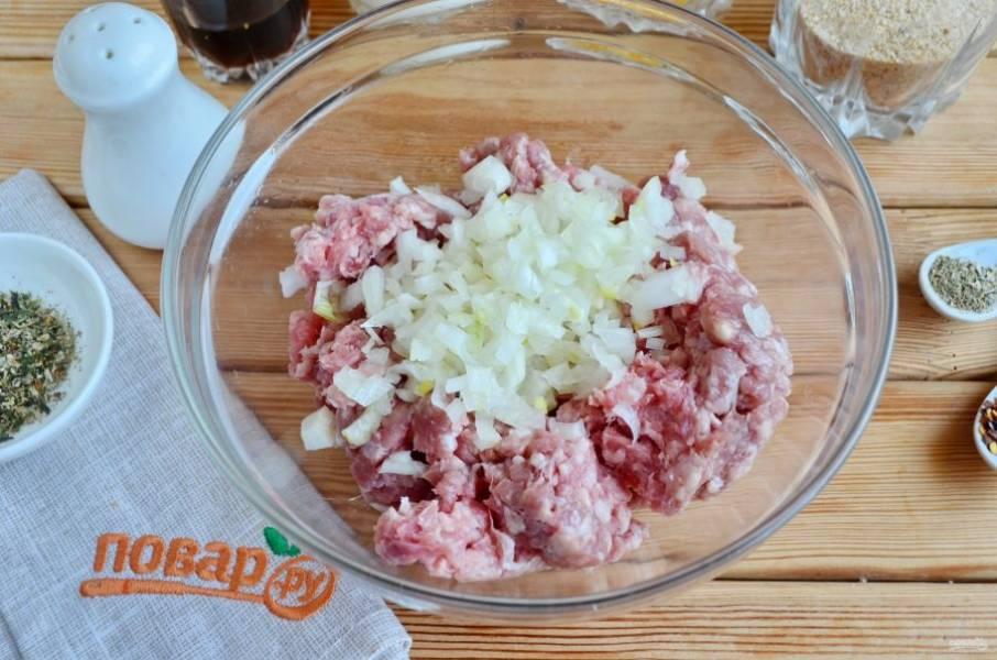 В говяжий фарш положите мелко порезанную луковицу.