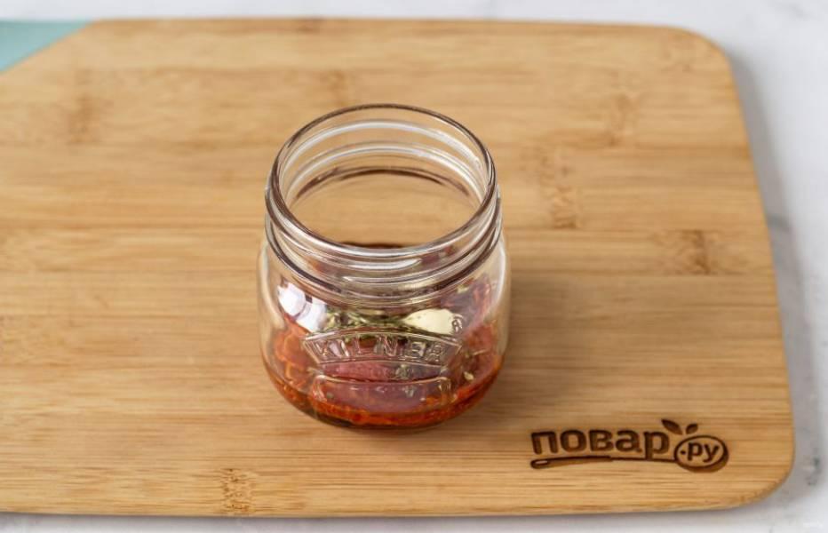 Подготовьте чистую стерилизованную баночку. Выложите слоями томаты, очищенные зубчики чеснока и сушеные итальянские травы.