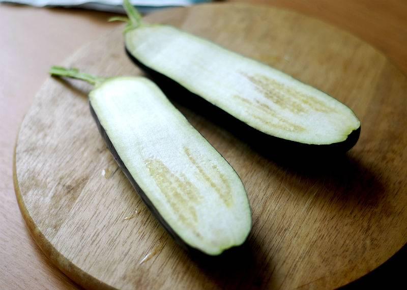 1. Баклажаны вымыть, обсушить немного и разрезать пополам. Сделать небольшие надрезы на мякоти и смазать кунжутным маслом.