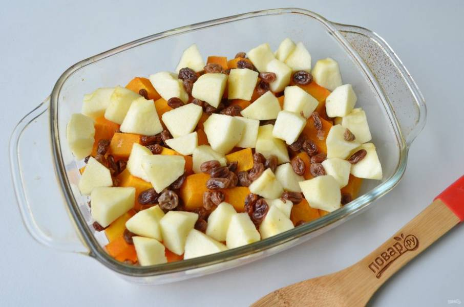 7. Положите сверху яблоки и изюм, и отправьте тыкву в духовку на 15 минут для размягчения яблок.